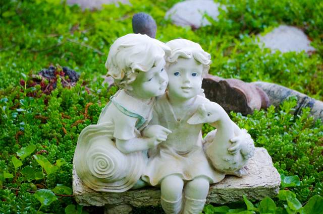 A Cute Figurine of a Little Boy and Girl in a Backyard