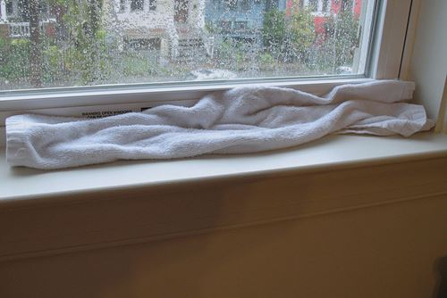 A Window Leaking on a Rainy Day Plugged by a Towel