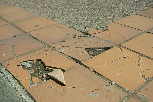 Broken and Cracked Tiles on a Laid Pathway